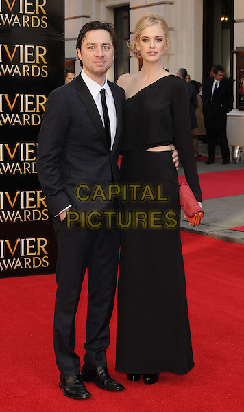 Zach Braff & Taylor Bagley.The Olivier Awards 2012, Royal Opera House, Covent Garden, London, England..April 15th, 2012.full length dress suit couple red clutch bag black one sleeve shoulder cut out away.CAP/CAN.©Can Nguyen/Capital Pictures.