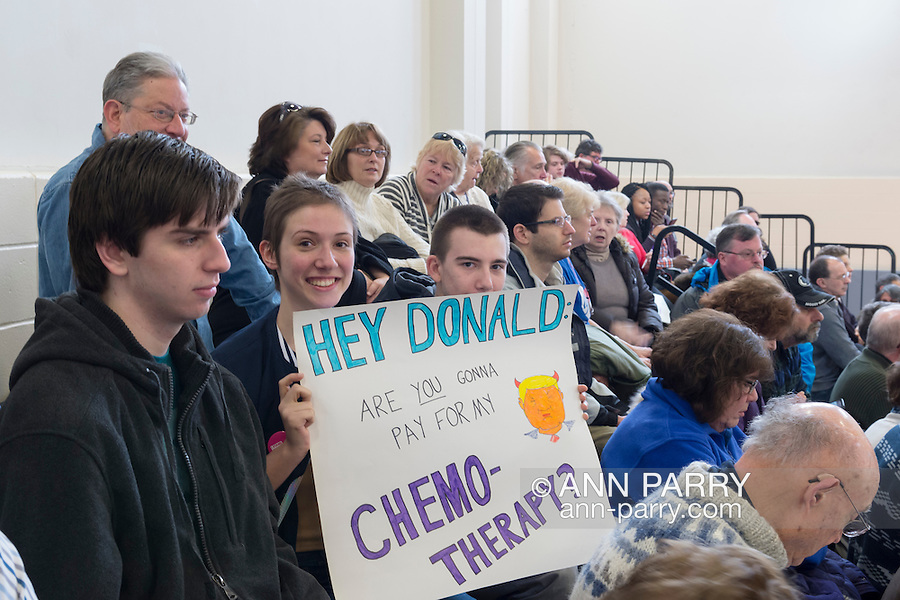 """Westbury, New York, USA. January 15, 2017.  BRIDGIT SQUITIRE, of West Islips holds a sign asking """"HEY DONALD, ARE YOU GONNA PAY FOR MY CHEMO-THERAPY?""""  at the """"Our First Stand"""" Rally against Republicans repealing the Affordable Care Act, ACA, taking millions of people off health insurance, making massive cuts to Medicaid, and defunding Planned Parenthood. Hosts were Reps. K. Rice (Democrat - 4th Congressional District) and T. Suozzi (Dem. - 3rd Congress. Dist.). It was one of dozens of Bernie Sanders' rallies nationwide for health care that Sunday."""