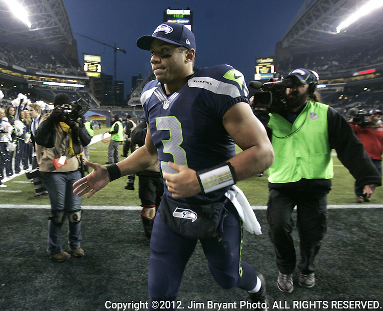 Seattle Seahawks Quarterback Russell Wilson runs into the locker room after their game against  St. Louis Rams  wide receiver Chris Givens after the game at CenturyLink Field in Seattle, Washington on December 30, 2012.   Wilson completed 15 of 19 passes for 250 yards, threw for one touchdown, rushed for 58 yards, sacked six times and ran for the game winning touchdown as the Seahawks came from behind to beat the Rams 20-13.     ©2012.   Jim Bryant Photo. All Rights Reserved.