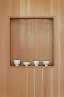 Understated white porcelain cups by Allison Paschke are displayed on a recessed shelf set in wood panelled wall.