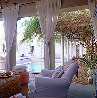 A comfortable sitting area on an outside terrace with a view over the courtyard swimming pool