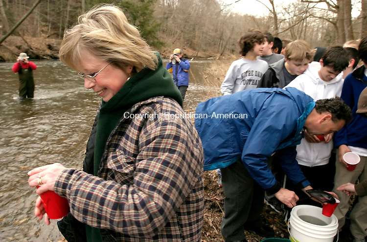 SOUTHBURY, CT--05 APRIL 2007--040507JS05- Susan Johnson a teacher at Memorial Middle School in Middlebury, preparse to releases one of 98 brook trout into the Pomperaug River at the Bent of the River Audubon Center in Southbury. The seventh graders, from the middle school's Life Science class, raised the trout as part of Trout in the Classroom educational program with the Naugatuck Pomperaug Chapter of Trout Unlimited. <br /> Jim Shannon / Republican-American