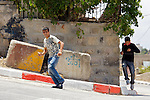 Palestinian youths flee from the retribution of (unseen) IDF soldiers after collecting rocks to throw at them following a nonviolent demonstration against Israel's controversial separation barrier in the West Bank town of Beit Jala near Bethlehem on 27/06/2010.