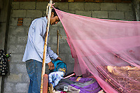 Ratna Baniya (28) prepares his daughter's school bag while his youngest daughter Sapana Baniya (2 months) sleeps in a basket in their temporary home in Chautara, Sindhupalchowk, Nepal on 29 June 2015. The three girls lost their mother during the April 25th earthquake that completely levelled their house. Aastha was buried under the rubble together with her mother but Aastha survived. As their father Ratna Baniya (28) cannot care for the children on his own, SOS Childrens Villages has since been supporting the grandmother with financial and social support so that she can manage to raise the children comfortably and ensure that they will all be schooled. Photo by Suzanne Lee for SOS Children's Villages