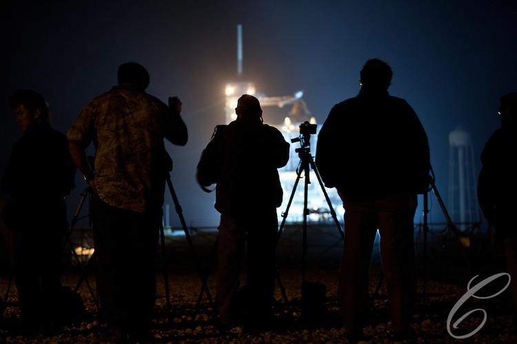 Photographers wait for the Discovery to be revealed on the eve of its launch from Kennedy Space Center for the final time on February 24, 2011.  Discovery's mission takes it to the International Space Station (ISS) to deliver the PMM module and Robonaut 2.