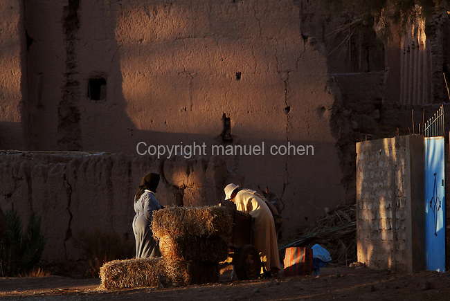 Old man and woman with hay bales at night time in Skoura, Ouarzazate province, Souss-Massa-Draa, Morocco. Skoura is a fertile oasis lined with immense palm groves. Picture by Manuel Cohen
