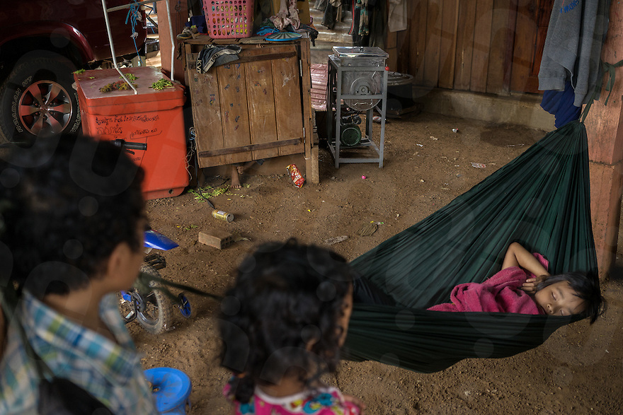 August 25, 2015 - Srekor village, Stung Treng (Cambodia). A kid sleeps in one of the houses in Srekor village. The village and the sorrounding areas have been  will be soon be flooded because of the construction of the Lower Sesan II dam. The 400-MW dam—a joint venture between Cambodian businessman Kith Meng and China's Hydrolancang International Energy Co. Ltd.—is set to displace more than 5,000 villagers in Sesan district. Studies claim that the dam could seriously affect fisheries, and in turn the livelihoods of more than 100,000 residents living upstream and downstream of the dam. © Thomas Cristofoletti / Ruom