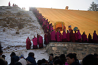 Crowds gather to watch Tibetan Buddhist monks unveil a huge Thangka, a painted image of Buddha displayed on a hillside, in Xiahe, Gansu, China.  The city is home to the Labrang Monastery, an important site in Tibetan Buddhism.