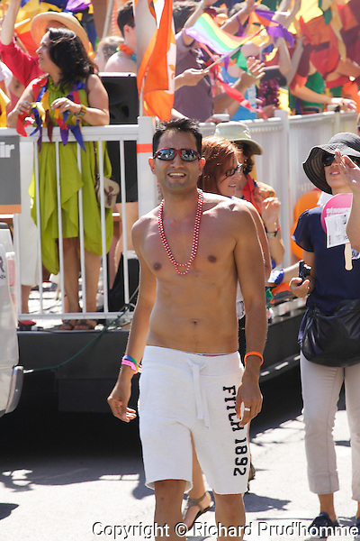 a young adult male walks along side a float in the Pride Parade
