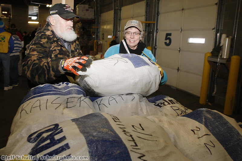 Wednesday, February 13, 2013.  Volunteers Diane Toebe and Dale Alter stack a bag of musher's food on the appropriate  stack at Airland Transport in Anchorage.  Iditarod 2013.