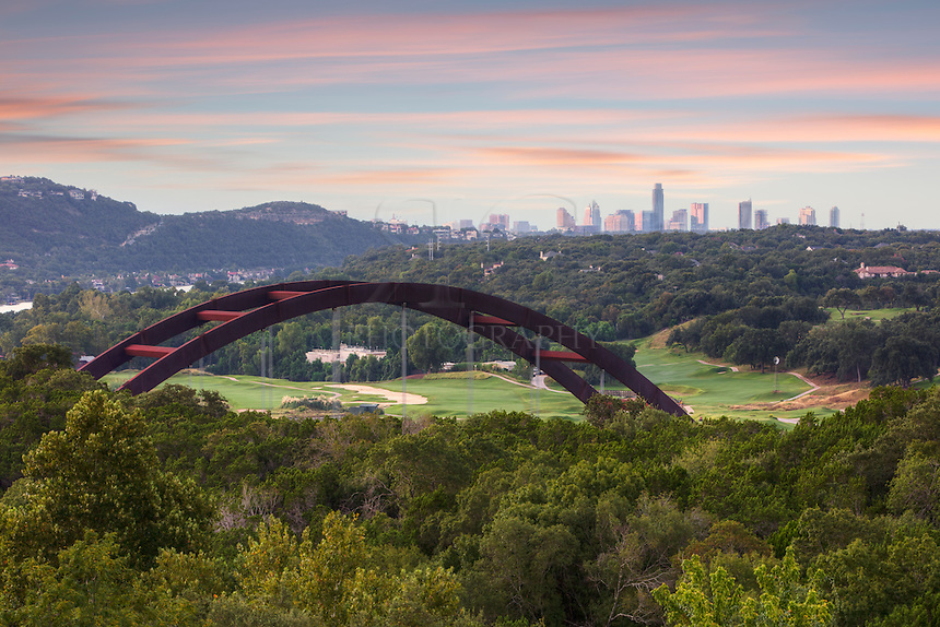 Pennybacker Bridge, also known as the 360 Bridge, rises from the trees along the Colorado River. In the distance, the highrises of downtown Austin, Texas, rise into the cool morning air.