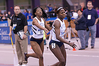 Dereka Kelly hands off to anchor Michelle Cumberbatch in the 4x400.