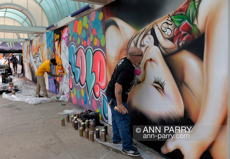Garden City, New York, USA. September 13, 2015. At right, JAMES SEXER RODRIGUEZ, street name SEXER1, from Bronx, NY, spray paints a mural of a woman, on the wall of urban art paintings by contemporary artists, outdoors at the United Ink Flight 915 Tattoo convention at the Cradle of Aviation Museum in Long Island. The word Paz, peace, is part of the woman's arm tattoo.