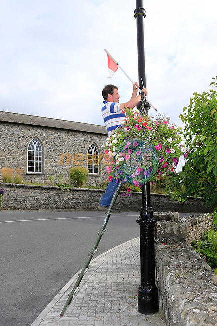 Moynalty village in Co Meath, winner of the Tidy towns 2013 Tom Lynch putting up flags after finding out that the Village had won.<br /> Picture Fran Caffrey www.newsfile.ie