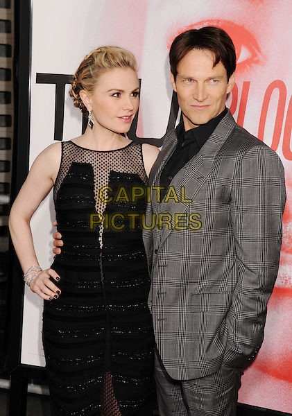 """Anna Paquin, Stephen Moyer.HBO's """"True Blood"""" Season 5 Premiere, Hollywood, California, USA..May 30th, 2012.half length black dress sheer polka dot sleeveless grey gray suit married husband wife pregnant hand on hip.CAP/ROT/TM.©Tony Michaels/Roth Stock/Capital Pictures"""