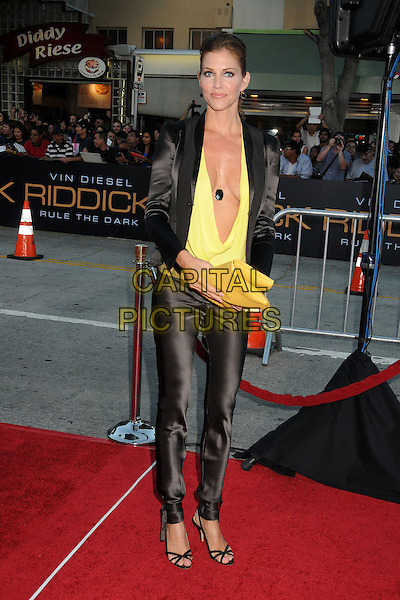Tricia Helfer<br /> &quot;Riddick&quot; Los Angeles Premiere held at the Regency Village Theatre, Westwood, California, USA,<br /> August 28th 2013.<br /> full length suit black trousers blazer jacket top yellow plunging neckline cleavage clutch bag<br /> CAP/ADM/BP<br /> &copy;Byron Purvis/AdMedia/Capital Pictures