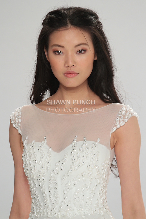 "Beauty shot: model walks runway in Shannon - an off white A-line tulle dress with cap sleeves and a full gathered skirt and pockets embellished with touches of crystal embroidery and silk flower appliques, from the Tony Ward Fall 2016 ""A Mid-Summer Night's Dream"" bridal collection on April 18, 2016 at Kleinfeld Bridal during New York Bridal Fashion Week Spring Summer 2016."