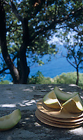 Slices of melon sit ready to eat on top of a pile of simple wooden plates on the stone table of the terrace
