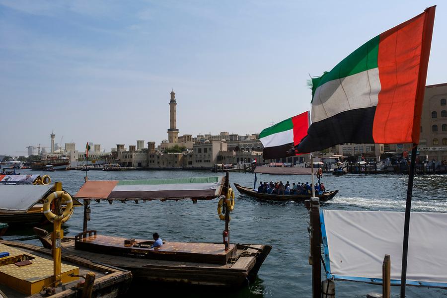 UNITED ARAB EMIRATES, DUBAI - CIRCA JANUARY 2017: The Dubai Creek in Deira and the United Arab Emirates Flag.