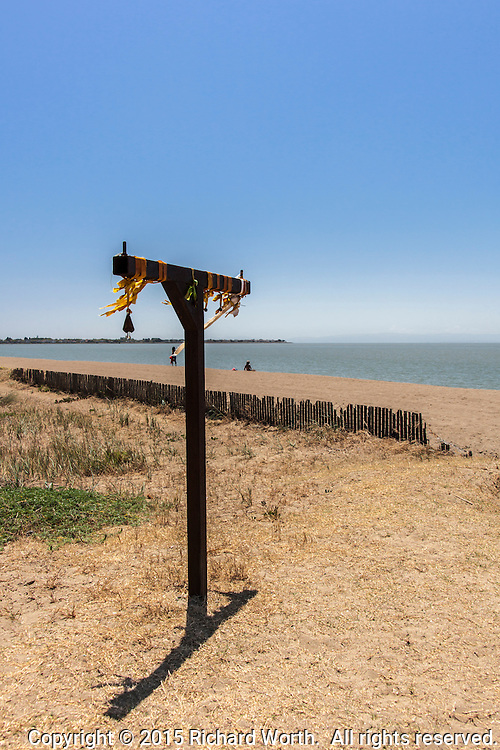 Bells dangle from ribbons tied to an iron T standing at an entrance to the Robert W. Crown Memorial State Beach in Alameda, California, along the eastern shores of San Francisco Bay.