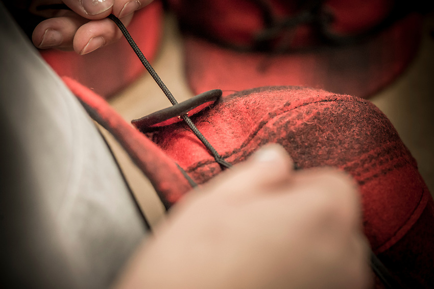 The final step in the Stormy Kromer manufacturing process hand tying the ear flap string at the Ironwood, Michigan production facility.