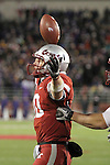 Jeff Tuel, Washington State sophomore quarterback, reacts (by appearing to balance the football on top of his helmet) after scoring a touchdown during the Apple Cup Pac-10 conference battle against arch-rival Washington at Martin Stadium in Pullman, Washington, on December 4, 2010.  The Huskies prevailed in the contest by scoring a late touchdown to break a 28-28 tie to win, 35-28.