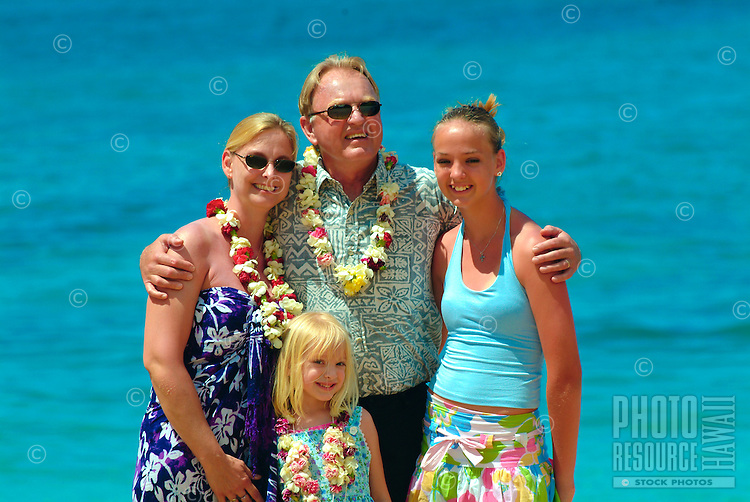 Tourist family with parents and two daughters on the beach