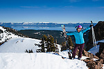 Woman in blue jacket holding skis on the high traverse while spring skiing at Alpine Meadows ski resort, California, with Lake Tahoe in the background.