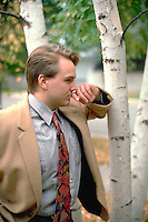 22 year old man by birch trees in front of his house thinking about work.  St Paul Minnesota USA