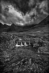 A rushing stream flows down from the Black Cuillin Mountain Range.  Black cloudy sky overhead