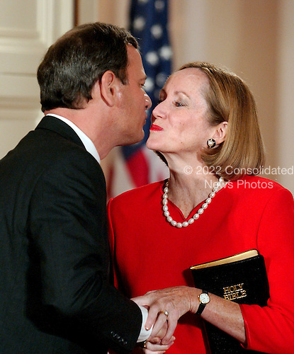 Washington, DC - September 29, 2005 -- John Glover Roberts, Jr., left, shares a kiss with his wife, Jane Sullivan Roberts, right, after he was sworn-in as the 17th Chief Justice of the United States by Associate Justice John Paul Stevens in the East Room of the White House in Washington, D.C. on September 29, 2005..Credit: Ron Sachs / CNP