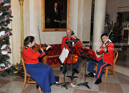 "Washington, DC - December 3, 2008 -- A string trio plays holiday favorites under a portrait of former United States President George H.W. Bush during a media preview of the 2008 holiday decorations and tasting event on the State Floor of the White House in Washington, D.C. on Wednesday, December 3, 2008.  The theme of this years decorations is ""a Red, White, and Blue Christmas""..Credit: Ron Sachs / CNP"