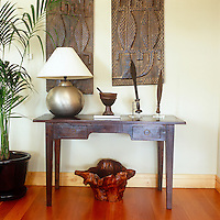 Carved reliefs hang on the wall while antique daggers are displayed on a desk in the living room of this London apartment