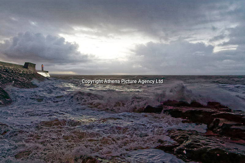 Pictured: Waves crash against the promenade wall and lighthouse in Porthcawl, Wales, UK. Thursday 18 January 2018<br /> Re: Strong winds have been affecting parts of the UK.