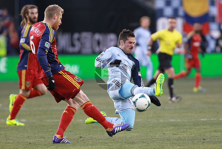 Sporting KC midfielder Benny Feilhaber (10) runs in front of Real Salt Lake defender Nat Borchers (6) to block his kick in the second half.  Sporting KC defeated Real Salt Lake in a shootout after the score was tied 1-1 at the end of regulation play in the MLS Cup 2013 championship held at Sporting Park in Kansas City, Kansas on Saturday December 7, 2013.