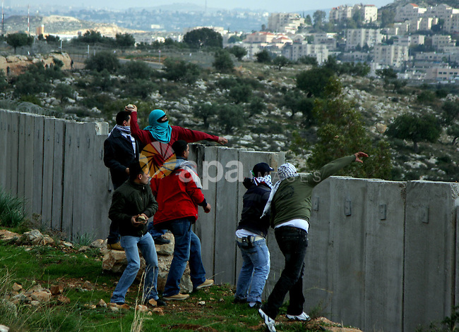 Palestinian demonstrators hurl stones at Israeli soldiers, not seen, during a demonstration against Israel's separation barrier in the West Bank village of Nilin near Ramallah, Friday,January 1, 2010. Photo by Issam Rimawi