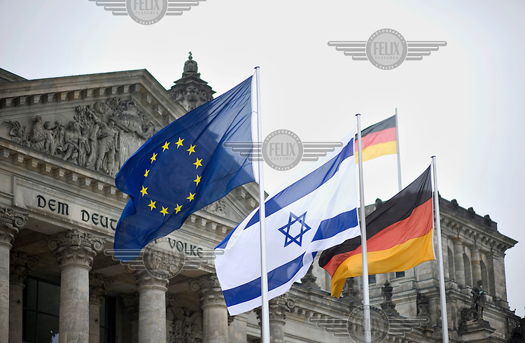 The German, Israeli and European Union flags fly outside the Bundestag.