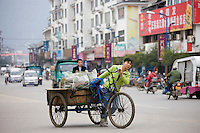 Woman with bicycle delivery cart in Yangshuo street, China