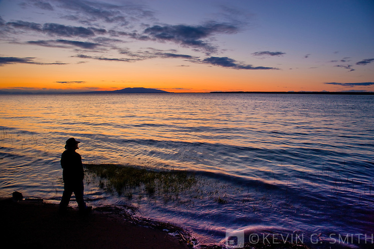 Man standing on the shoreline of Knik Arm at sunset, Mount Susitna or Sleeping Lady in the distance across the  water, taken from the Tony Knowles Coastal Trail, late summer, Anchorage, Southcentral Alaska, USA. Model Released