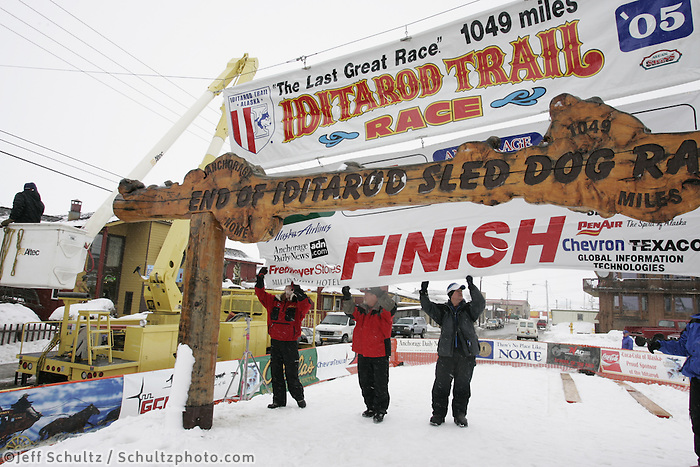 Race officials and volunteers raise the finish line banner in preparation for the finish of the Iditarod, expected sometime Wednesday morning.  2005 Iditarod Trail Sled Dog Race.