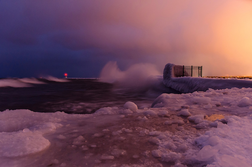 Wind, waves and snow along the Lake Superior shoreline at the Presque Isle Breakwater. Nearby city light pollution illuminated the sky and help create this neat effect. Marquette, MI