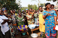 Community nutrtition group leader, Elyse Musandji (right) showing women in Mabundu how to produce milk from peanuts. Peanuts are a locally grown product which are typically roasted and sold as a roadside snack. But they can be turned into a nutritious milk - which children love - by soaking them in water, grinding them in a mortar and filtering the paste.