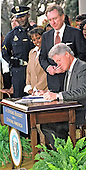 United States President Bill Clinton signs the Consolidated Appropriations Act for Fiscal Year 2000, providing funding for education, public safety, the environment, international leadership, health care and other priorities in the Rose Garden of the White House in Washington, DC on November 29, 1999.  The President also pushed Congress to complete his agenda when it returns in January, 2000.  US Senator Arlen Spector (Republican of Pennsylvania) looks on. <br /> Credit: Ron Sachs / CNP