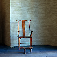 A Chinese chair and footstool are placed against a curved wall of textured plaster