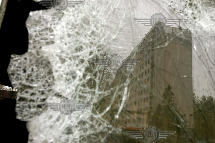 The housing project apartment block where two teenagers, Moushin, 15, and Laramy, 16, lived is seen through a shattered window. The two teenagers were killed when the motorcycle they were riding collided with a police car. The deaths sparked widespread rioting and violence throughout this and other Paris suburbs.