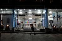 Nightime landscape view of a woman walking past a Softbank store in Harajuku following the 311 Tohoku Tsunami in Tokyo, Japan  © LAN