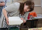 Learning Support Assistant pouring PVA glue, Art & Craft class for a learning support group, Adult Learning Centre, Guildford, Surrey.