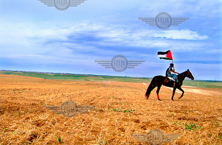 """A Bedouin youngster carries a Palestinian flag as he rides his horse on the """"Day of the Land"""".  This day is marked every year by Israeli-Arabs and Palestinians to commemorate the loss of Arab land to the state of Israel.."""