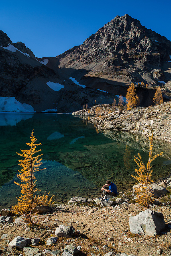 A young adult male filters water out of Wing Lake in Washington State's North Cascade mountain range with Black Peak in the background.