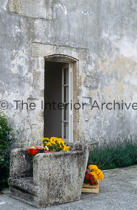 A stone armchair outside the back door of an 18th century French country house has been filled with sunflowers and dahlias from the garden